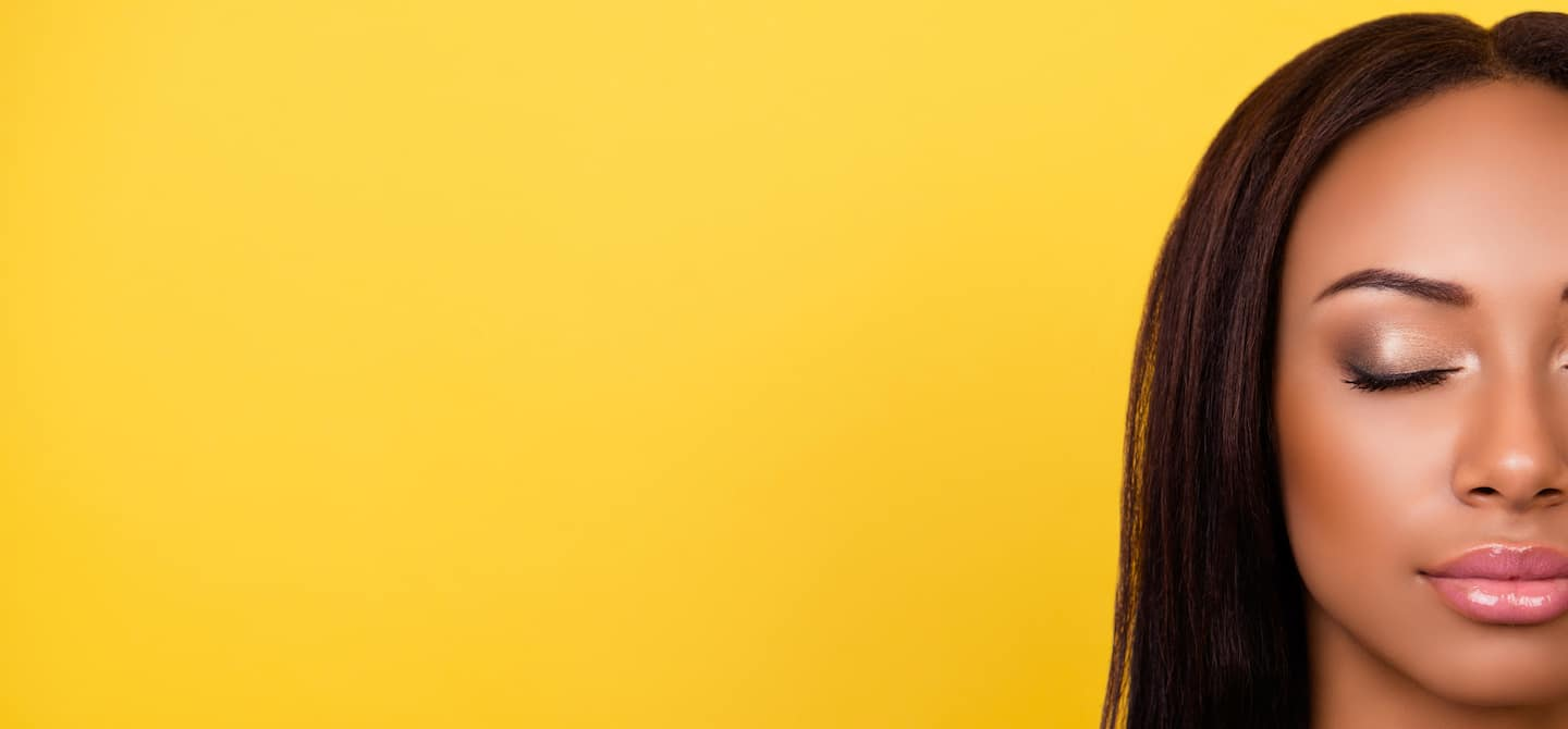Woman with beautiful skin and eyes closed in front of yellow backdrop