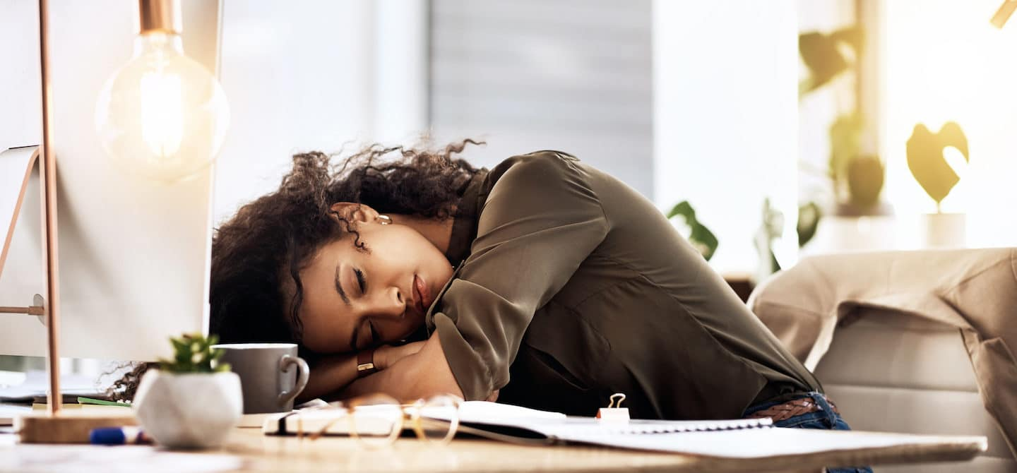 Woman with vitamin B12 deficiency asleep at desk