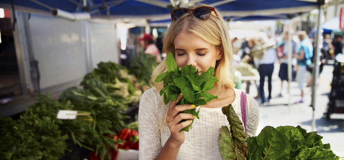 Woman smelling fresh mint at farmer's market before meal prep