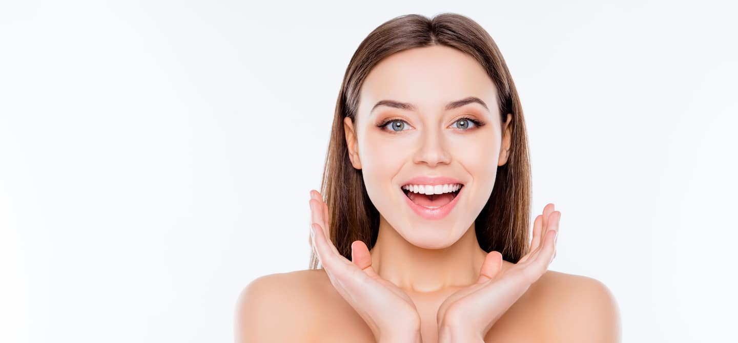 Woman looking happy into camera because taking collagen is giving her firm, bouncy skin