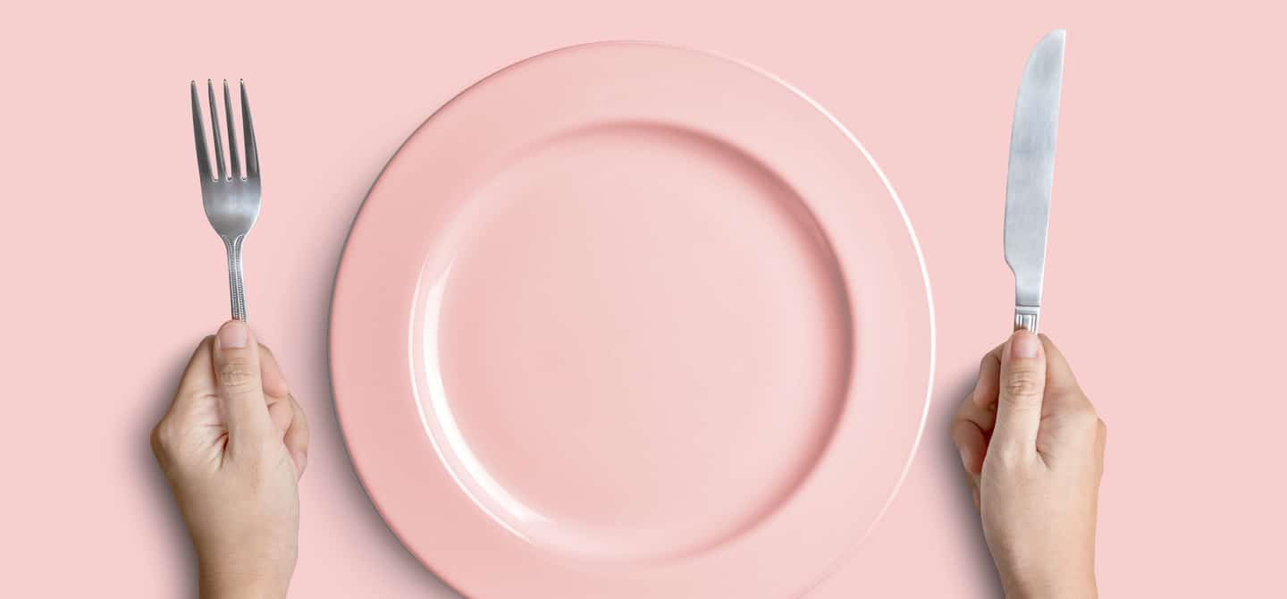 Empty pink plate with view of woman's hands holding fork and knife