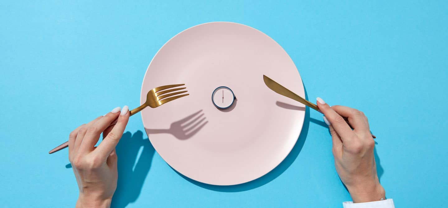 Woman's hands holding gold fork and knife in front of pink plate with a clock on it, signifying intermittent fasting