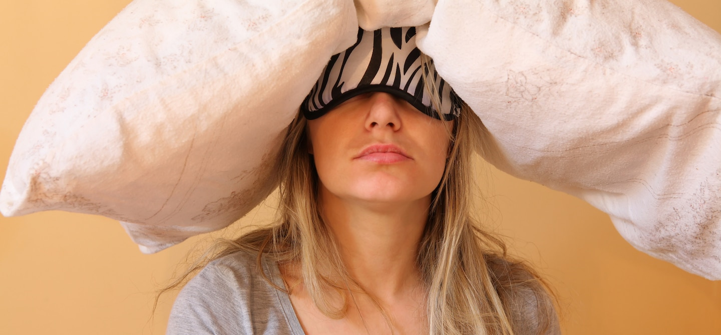 Woman wearing eye mask and pillow on her head feeling hungover