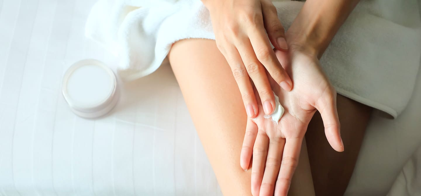 Woman moisturizing her hands with vitamin E skincare product