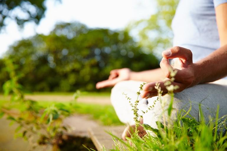 Man meditating outside in grass