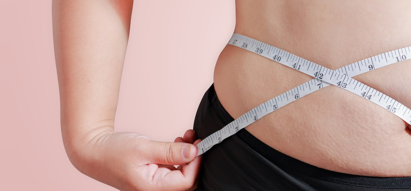 Woman measuring her torso with a tape measure, upset she's in a weight loss plateau