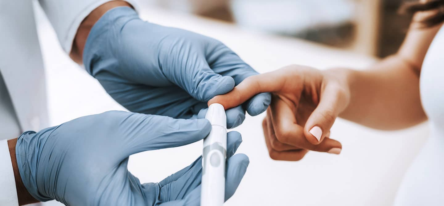 Doctor in gloves checking a woman's triglyceride levels with a finger blood test