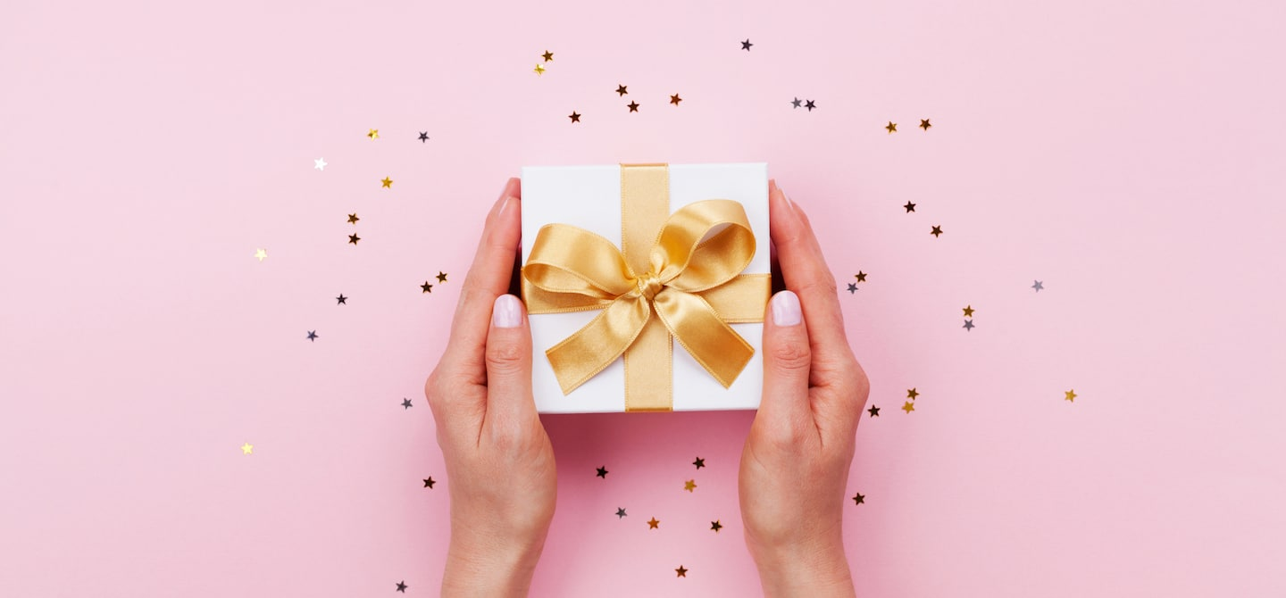 Hands holding a holiday gift with gold bow on pink background