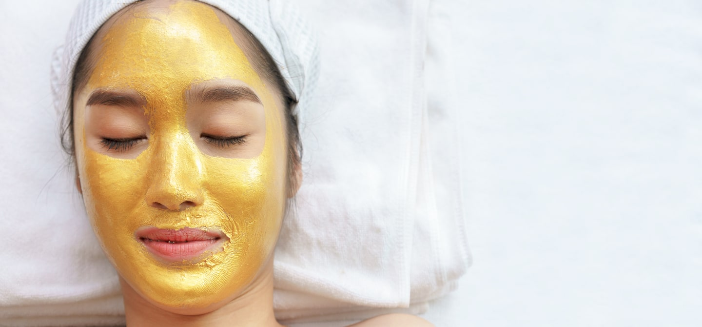 Woman at spa wearing a gold face mask