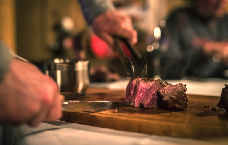 Man cutting steak after taking a bromelain supplement to improve digestion of protein