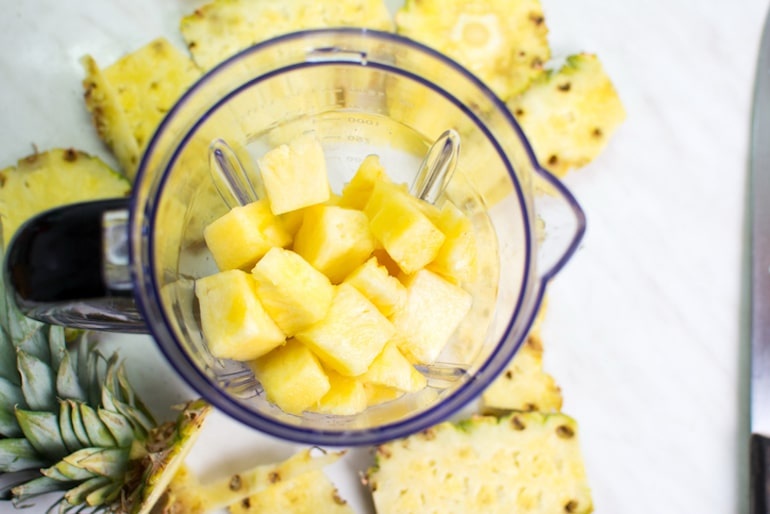 Chopped pineapple in a blender to make a DIY face mask for bromelain benefits for skin