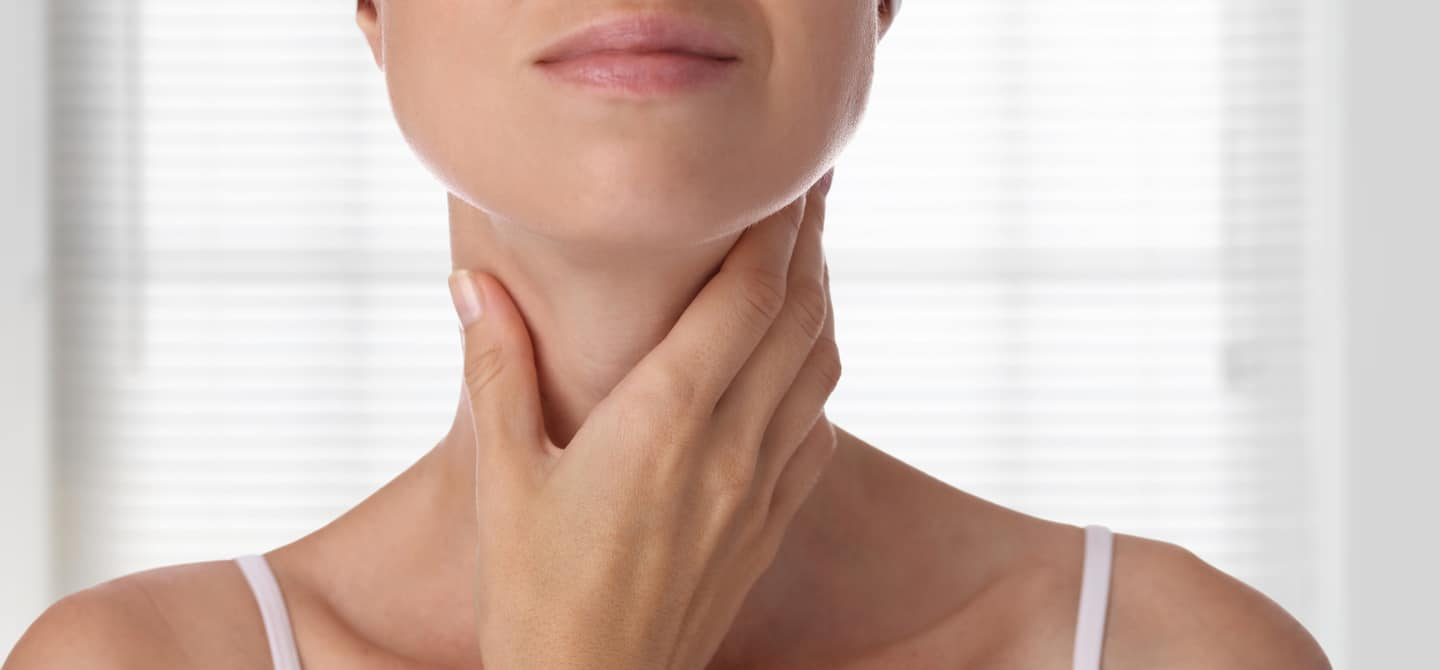 Woman checking on her thyroid glands under neck