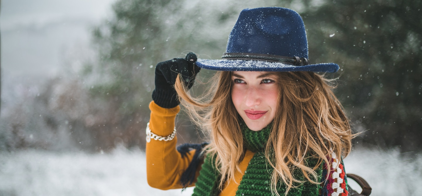 Woman holding onto her blue fedora hat in the snow after taking the best beauty supplements for winter