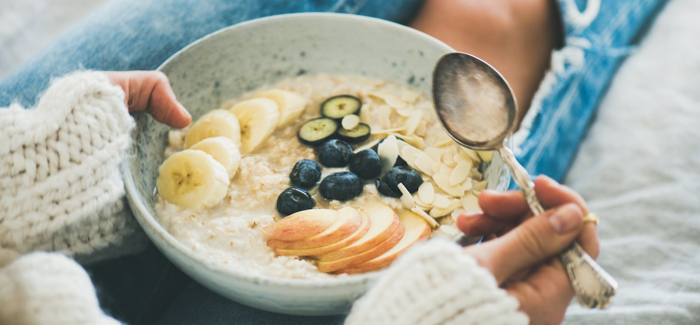 Woman practicing intuitive eating lifestyle with a bowl of oatmeal with fruit slices and berries