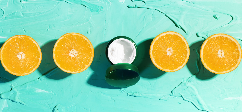 Skincare Acid Moisturizer flanked by 4 sliced oranges