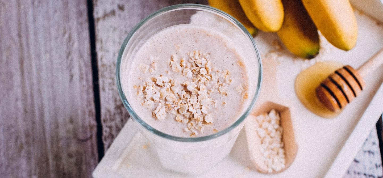 Homemade glass of oat milk next to honeycomb