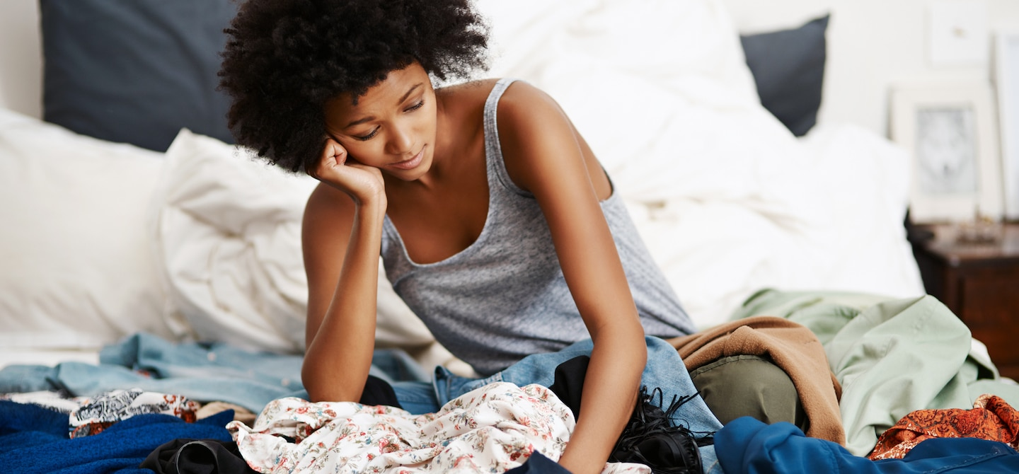 Woman sitting in bed amidst piles of clothes before clearing up with a Marie Kondo KonMari approach