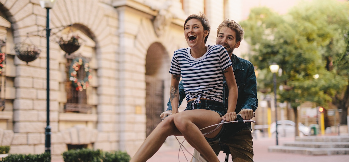 Woman riding on handlebars of her boyfriend's bike