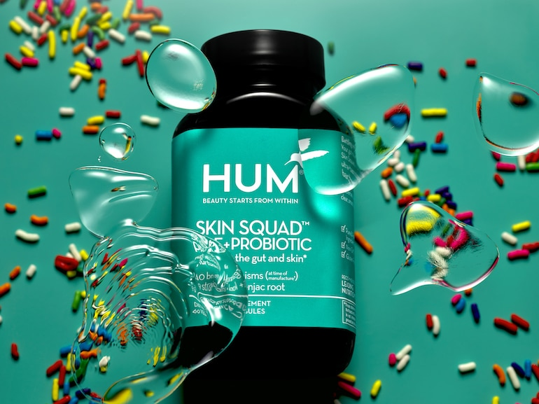 HUM Skin Squad Probiotic for Clear Skin, resting down on green background with rainbow sprinkles and bubbles