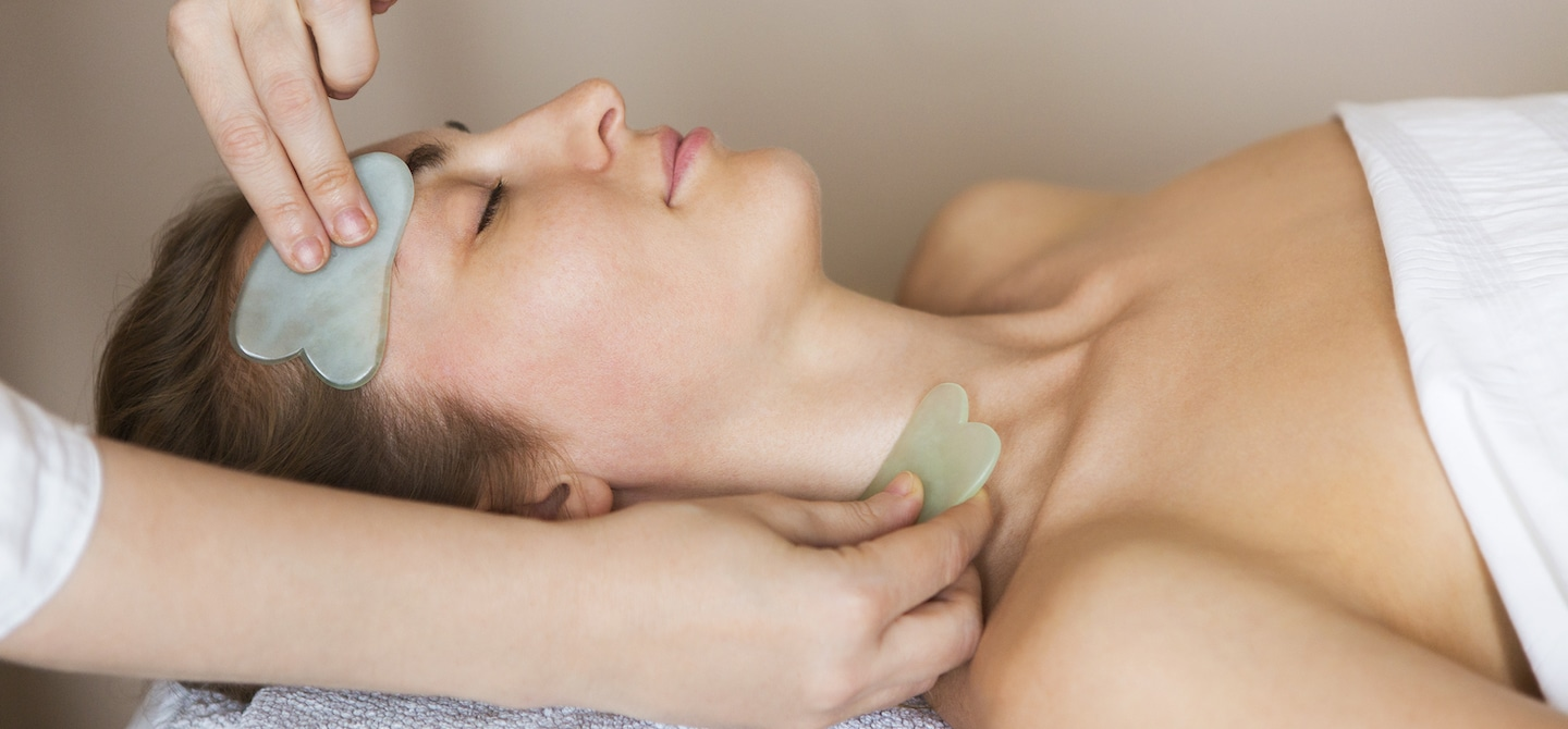 Woman getting a gua sha contour facial treatment by esthetician