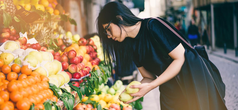 Woman picking fruit outside market on sidewalk