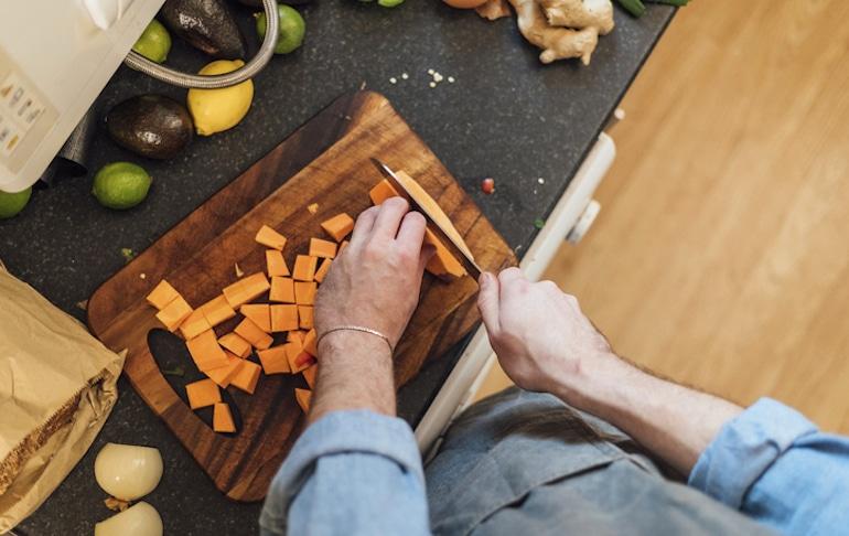 Man prepping sweet potato fries as part of a Trader Joe's meal plan