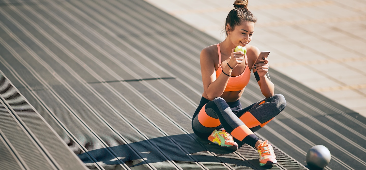 Woman wearing athleisure eating an apple and looking at phone before a workout