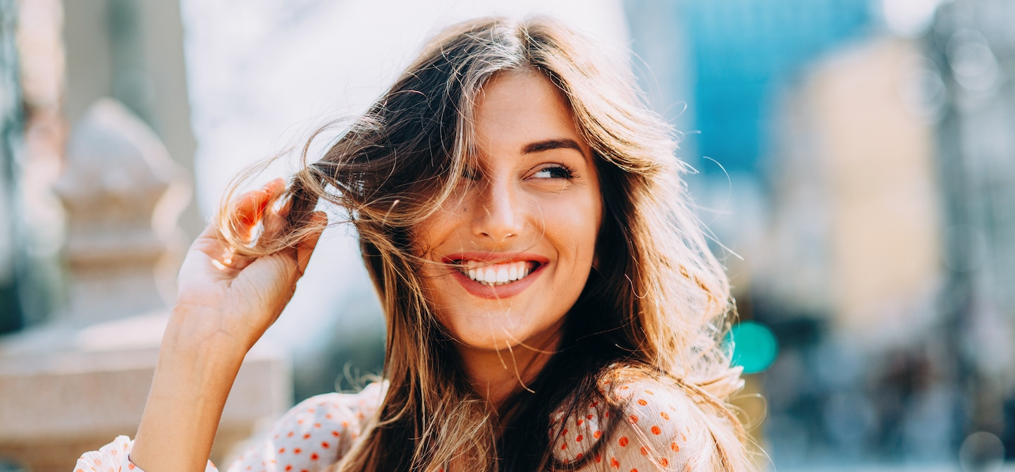 Woman smiling with healthy hair blowing in the wind