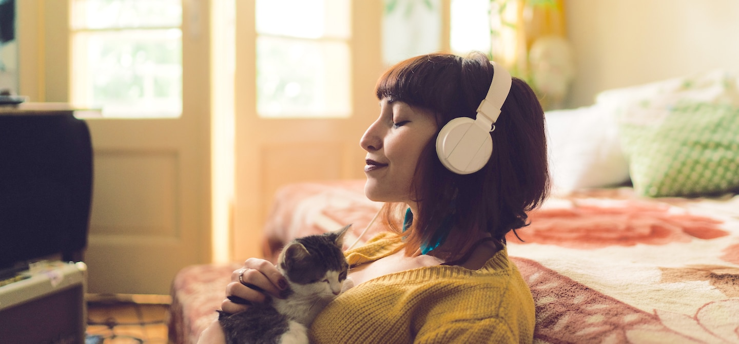 Woman on floor in bedroom holding kitten listening to meditation app on headphones