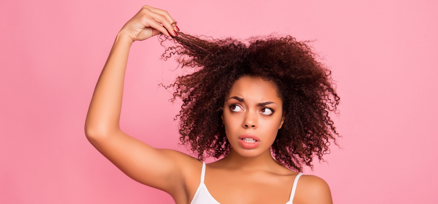 Woman with curly damaged hair holding her strands in angst against pink background