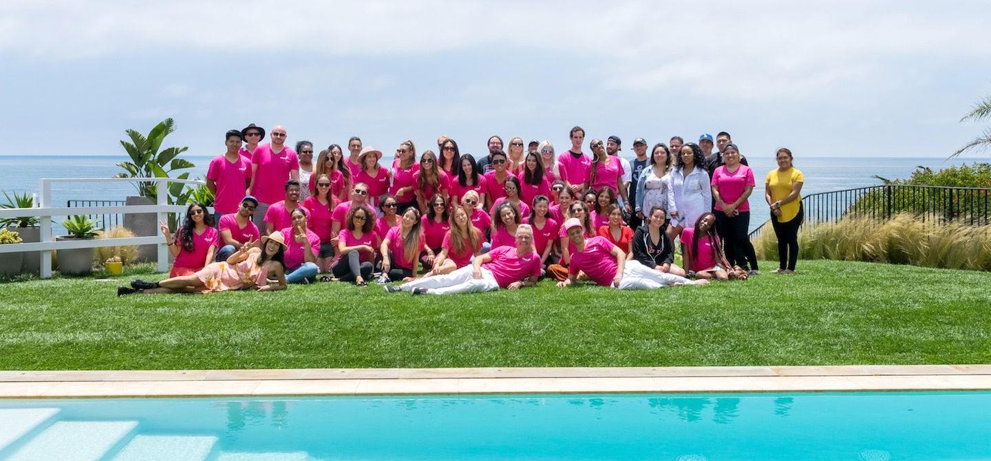 Group photo of HUM Nutrition team in pink shirts in front of pool in Malibu