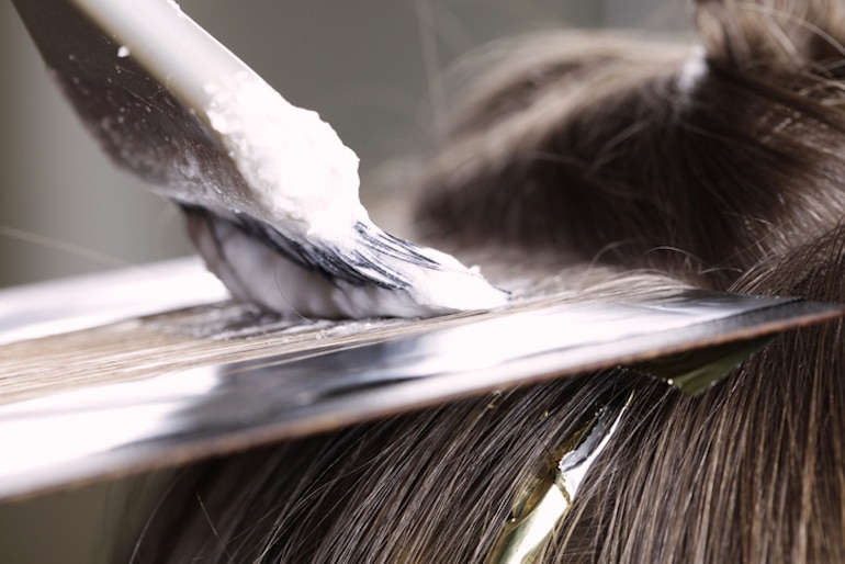 Woman getting her hair highlighted; chemicals can lead to hair damage and breakage