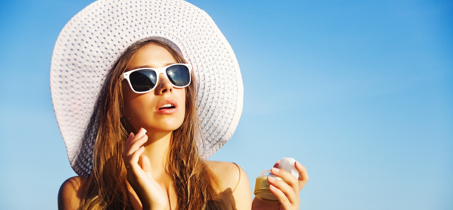 Woman in white sunhat and sunglasses applying sunscreen at the beach