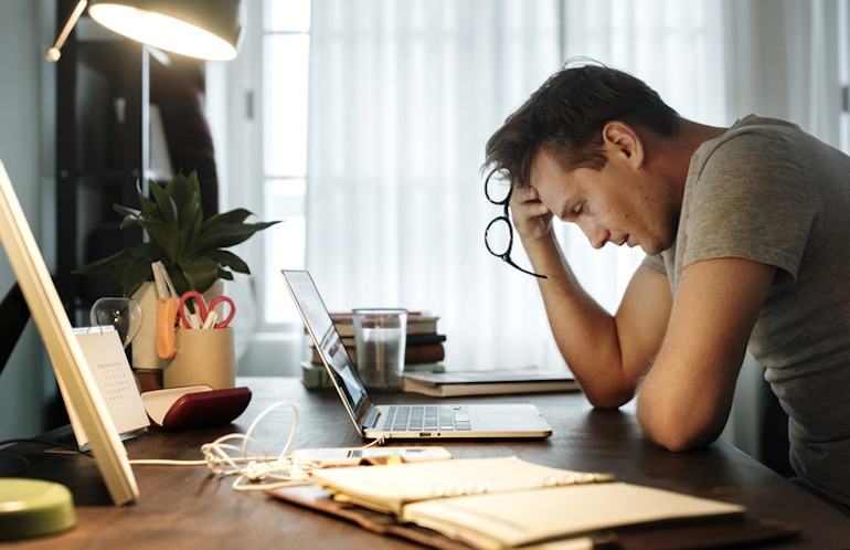 Stressed man suffering from symptoms of burnout at home in front of laptop