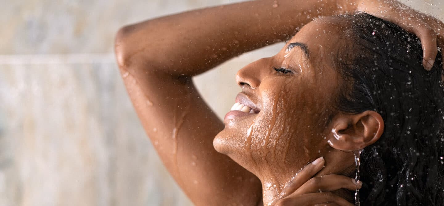 Woman in shower repairing damaged hair with targeted treatments and hair repair tips