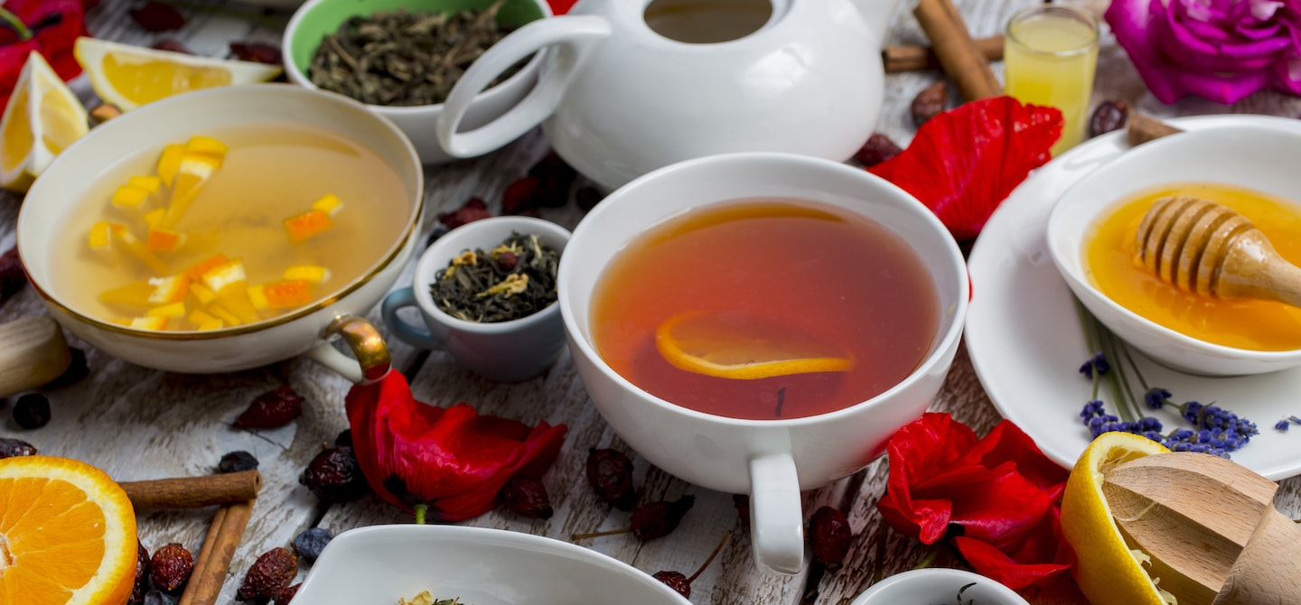 Assortment of teas on a white wooden table covered with flowers