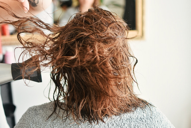 Redheaded woman getting her hair blown out