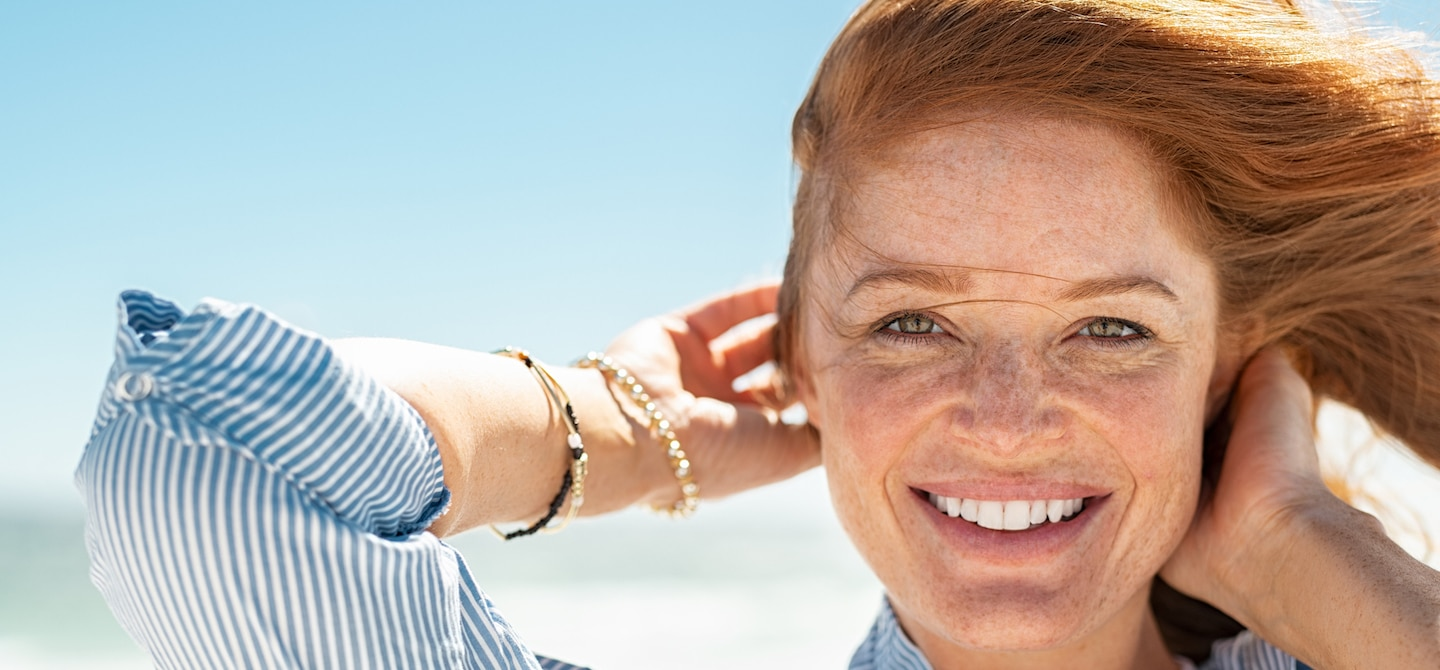Red-haired woman with clear skin and freckles smiling at beach in summer