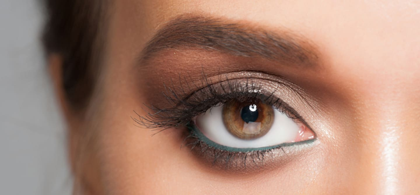 Close-up shot of woman's eye with long natural lashes and green eyeliner