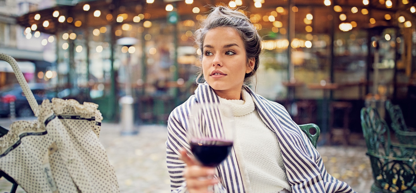 Woman sitting at chic restaurant outdoors with a glass of red wine