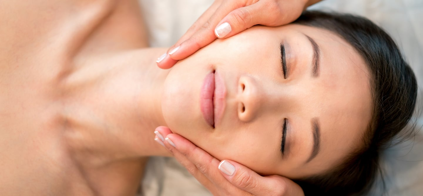 Overhead shot of woman with beautiful skin after microinfusion macial with esthetician holding her face