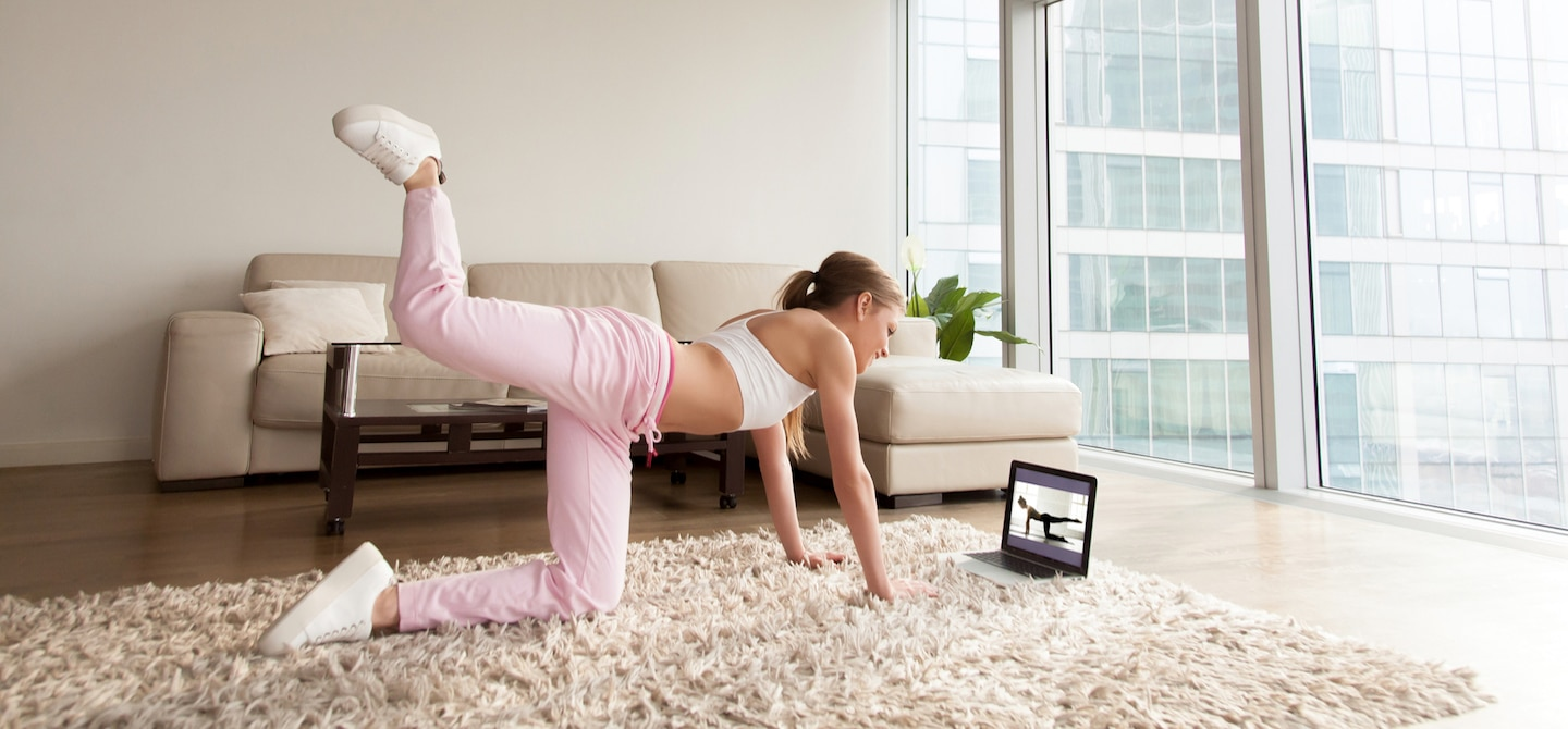 Woman in athletic gear working out in her living room with an online fitness program