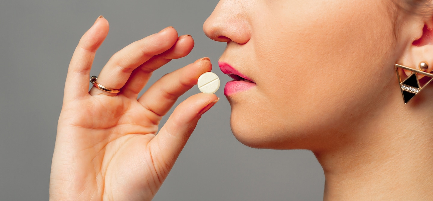 Woman wearing bright pink lipstick taking a vitamin for hormonal imbalance