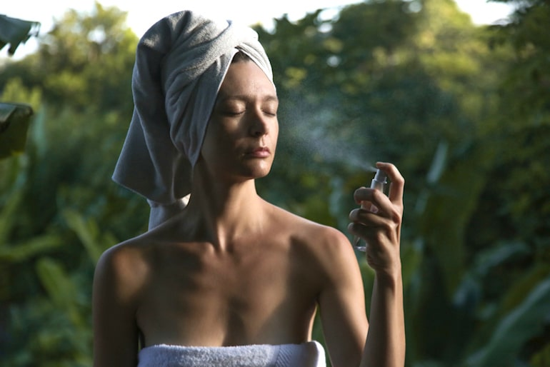 Woman hydrating skin after shower with a hyaluronic acid face mist