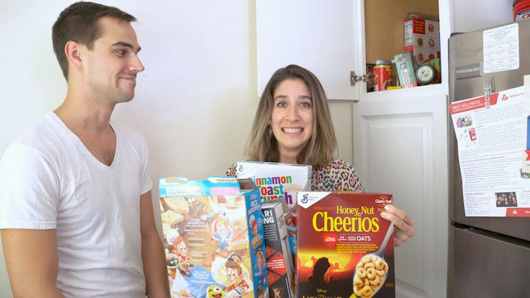 A registered dietitian tries to hold several boxes of sugary breakfast cereal from the pantry of a client.
