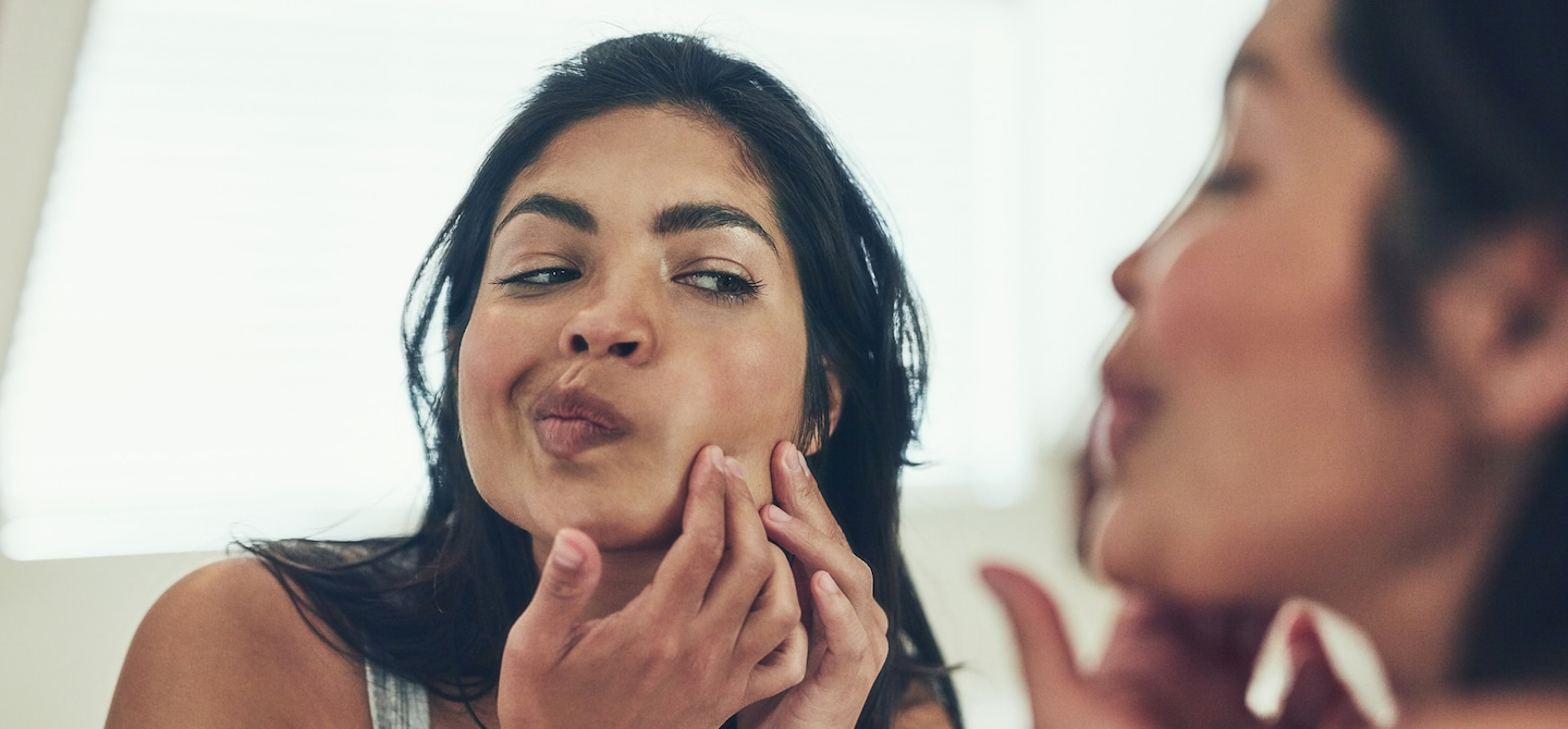 Woman looking in mirror for blackheads and breakouts