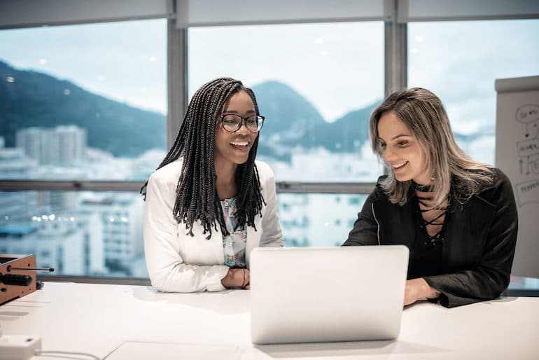 Two women at work delegating tasks and adopting productivity tips