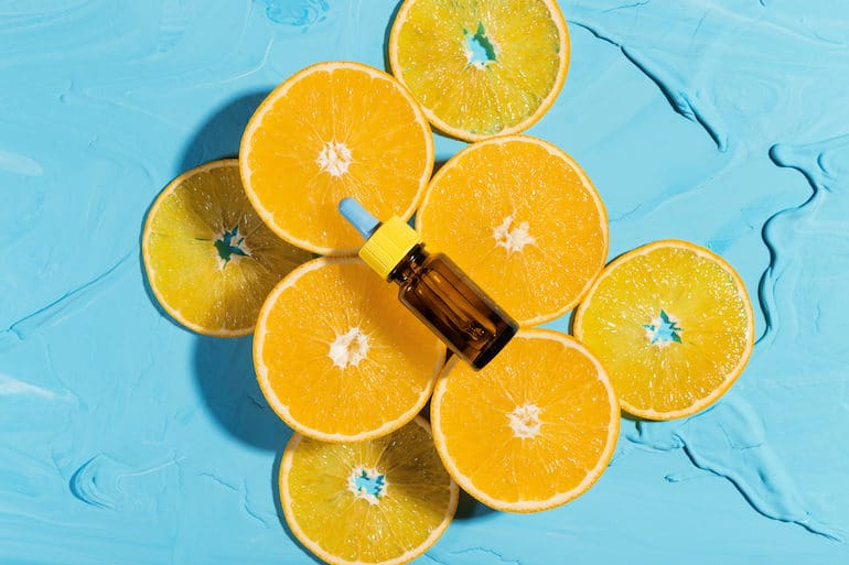 Orange Slices and Vitamin C Serum on Bright Blue Background