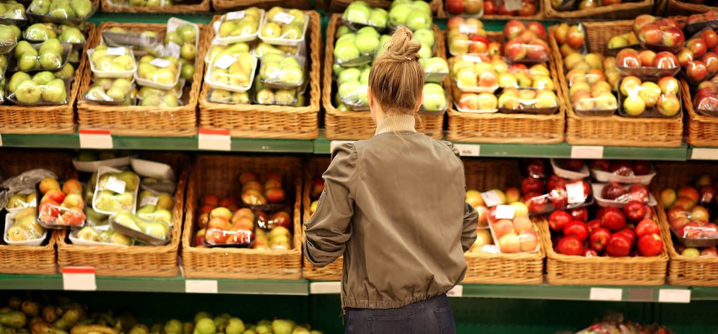 Woman looking at apples at grocery store