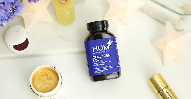 HUM Collagen Love bottle on beauty counter with makeup